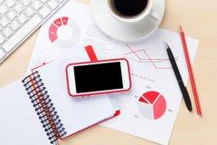 Arbetsplats för kontorsskrivbord med telefonen, diagram och kaffe royaltyfri fotografi