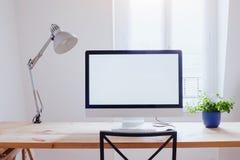 Arbetsplats i det moderna härliga kontoret, dator med den vita tomma tomma skärmen Royaltyfri Bild