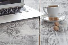 Arbetsplats med bärbara datorn och coffeecup på vit Royaltyfria Bilder