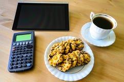 Arbetsplats med den minnestavlaPC, räknemaskinen, koppen kaffe och kakor Royaltyfria Bilder