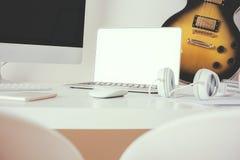 Arbetsplats med den tomma apparater och gitarren Arkivfoto
