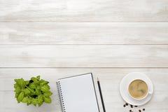 Arbetsplats med koppen kaffe, den inomhus växten, den tomma anteckningsboken och blyertspennan på träyttersida i bästa sikt arkivfoton