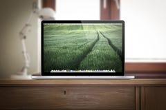 Arbetsplats med macbookpro-näthinnan på skrivbordet Royaltyfria Bilder