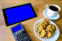 Arbetsplats med minnestavlaPC - blå ask, räknemaskin, kopp kaffe a Arkivfoto