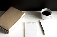Arbetsplats med notepaden, boken och koppen av svart kaffe på tabellen Arkivfoton
