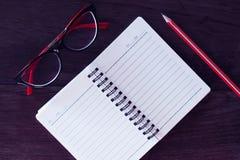 Arbetsplats: Röda exponeringsglas, anteckningsbok och blyertspenna på en tabell Royaltyfri Bild