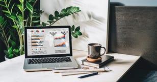 Arbetsplats utan folk, närbild av bärbara datorn med grafer, diagram, diagram på skärmen på den vita tabellen, skrivbord Arkivfoton
