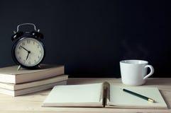 Arbetsplatsanteckningsbok, blyertspenna, böcker, kopp kaffe och klocka Fotografering för Bildbyråer