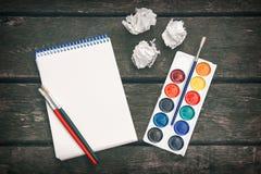 Arbetsplatsen av konstnären Never ger upp Notepad med det tomma arket av papper, kulör målarfärg, borstar och skrynkliga ark av p Arkivfoto