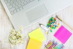 Arbetsskrivbord med tillförsel och blommor för kontor för bärbar datordator Arkivfoto