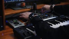 Arbetsstation för solid tekniker med det soundboardmidi pianot och det blandande brädet för solid tekniker Händer som vänder knop arkivfilmer