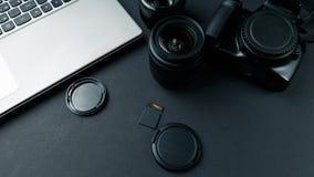 Arbetsutrymme p? den svarta tabellen av fotografen Minsta workspace med b?rbar dator-, kamera- och linskopieringsutrymme p? m?rk  royaltyfri fotografi