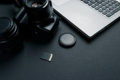 Arbetsutrymme p? den svarta tabellen av fotografen Minsta workspace med b?rbar dator-, kamera- och linskopieringsutrymme p? m?rk  fotografering för bildbyråer