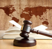 Arbitrate. Wooden gavel on a background map of the world Royalty Free Stock Image