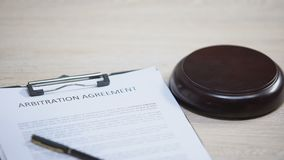 Arbitration agreement document on table, gavel striking on sound block, dispute
