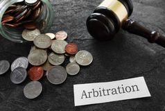 Arbitration news headline with coins and gavel. Coins and legal gavel with Arbitration news headline Royalty Free Stock Photos