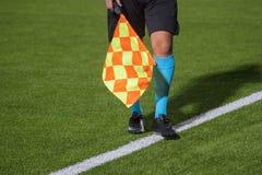 Arbitre adjoint marchant le long de la ligne de touche pendant un tapis du football image stock