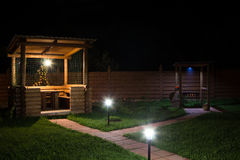 Arbor and barbecue in backyard at night Stock Images