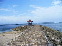 Arbor on the beach of Bali. A beautiful gazebo, a gazebo on the shore, a beautiful sea, the Indian Ocean, waves on the ocean, a stone beach, a path to the sea Stock Photos