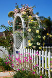 Arbor with Beautiful Flowers. A white picket fence and arbor with beautiful climbing roses and other flowers, a yard with a green lawn, and a blue sky Stock Images