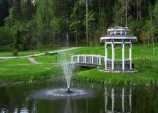 Arbor with a bridge on a pond. With a fountain Stock Photos