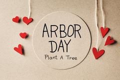 Arbor Day message with small hearts. Arbor Day message with handmade small paper hearts royalty free stock photos