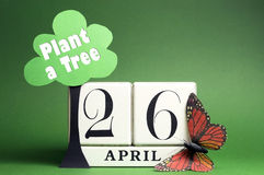 Arbor Day, plant a tree on April 26 with white block calendar, tree, butterfly and message against a green background. royalty free stock photo