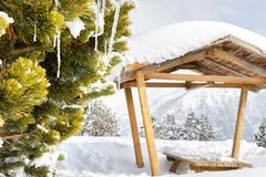 Arbor in the mountains in the snow among the firs. Wooden canopy among the snowdrifts in a frosty sunny day stock photography