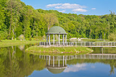 Arbor reflected in the smooth water Stock Images