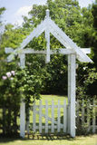 Arbor in Yard. A gated arbor entrance into a spacious green lawn. Vertical shot Stock Photo