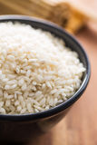 Arborio rice in bowl. Arborio rice in bowl on wooden table Royalty Free Stock Image