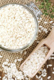 Arborio rice for risotto. Italian rice for risotto - Arborio - in a glass jar with a wooden scoop. Overhead view Royalty Free Stock Images