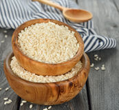Arborio rice. Uncooked Arborio rice in a wooden bowl on a gray table Royalty Free Stock Photo