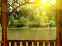 Arbour on the bank of the river. In abeam of the sun Royalty Free Stock Photography