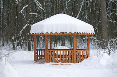 Arbour in the winter forest. Brown wooden arbour with benches inside in the winter forest Stock Photography