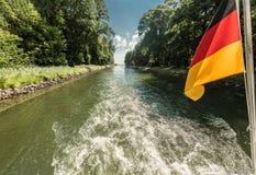 Arbre d'entraînement d'un bateau sur un passage de canal avec onduler le drapeau de l'Allemagne photo libre de droits