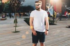 Arbre dans le domaine Le jeune homme barbu de hippie habillé dans le T-shirt et des lunettes de soleil blancs est des supports su photographie stock libre de droits