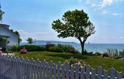 Arbre dans un jardin donnant sur Great Lakes un jour venteux avec des phares à l'arrière-plan images stock