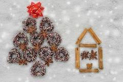 Arbre de biscuits de Noël près d'une maison faite par la cannelle avec le fond neigeux Image stock