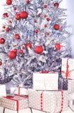 Arbre de Noël argenté avec des cadeaux avec les arcs rouges photos libres de droits