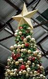 Arbre de Noël artificiel avec le rouge et les boules et l'étoile d'or Images stock