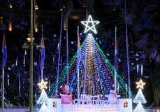 Arbre de Noël artificiel décoré des guirlandes avec une grande étoile rougeoyante sur le dessus L'inscription avec un souhait de  images stock