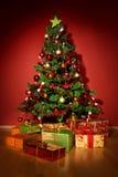 Arbre de Noël avec des cadeaux de Noël dans la chambre rouge Photo libre de droits