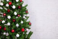 Arbre de Noël avec les boules colorées au-dessus du mur de briques blanc Images stock