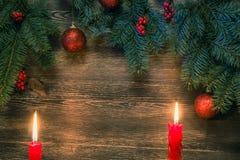 Arbre de Noël avec les boules rouges deux bougies de baies rouges et h bleu Photos libres de droits