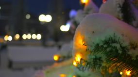 Arbre de Noël avec les ornements lumineux Arbre de Noël en parc dans la neige clips vidéos