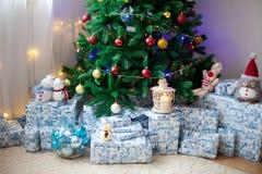 Arbre de Noël avec un bon nombre de présents sous l'arbre, lumières et Image stock