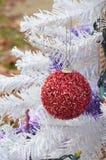 Arbre de Noël blanc accrochant de scintillement d'ornement rouge brouillé de Noël Photographie stock libre de droits
