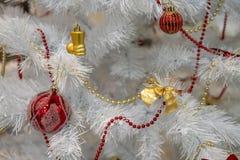 Arbre de Noël blanc décoré des jouets jaunes et rouges images stock