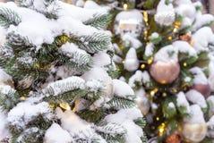 arbre de Noël couvert de neige avec des jouets et une guirlande photographie stock libre de droits